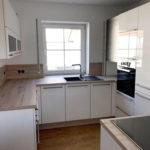 Schöne Küche mit lackierten Fronten und Absetzungen in Holz