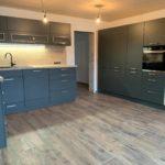 Küche in Dunkelgrau matt mit einem warmen, hellen Holzfarbton